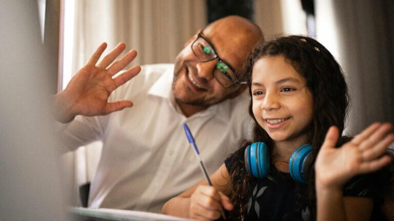 Menina abanada para a tela do computador com fones de ouvido no pescoço enquando o pai, ao seu lado, faz o mesmo.