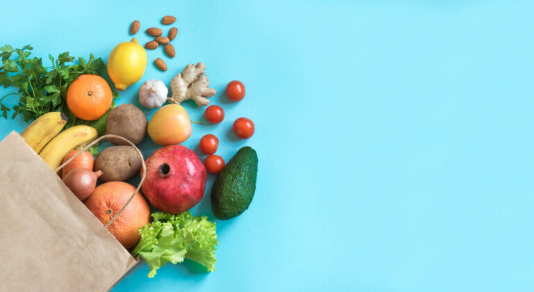 legumes e verduras sobre um fundo azul saindo de uma sacola de papel pardo