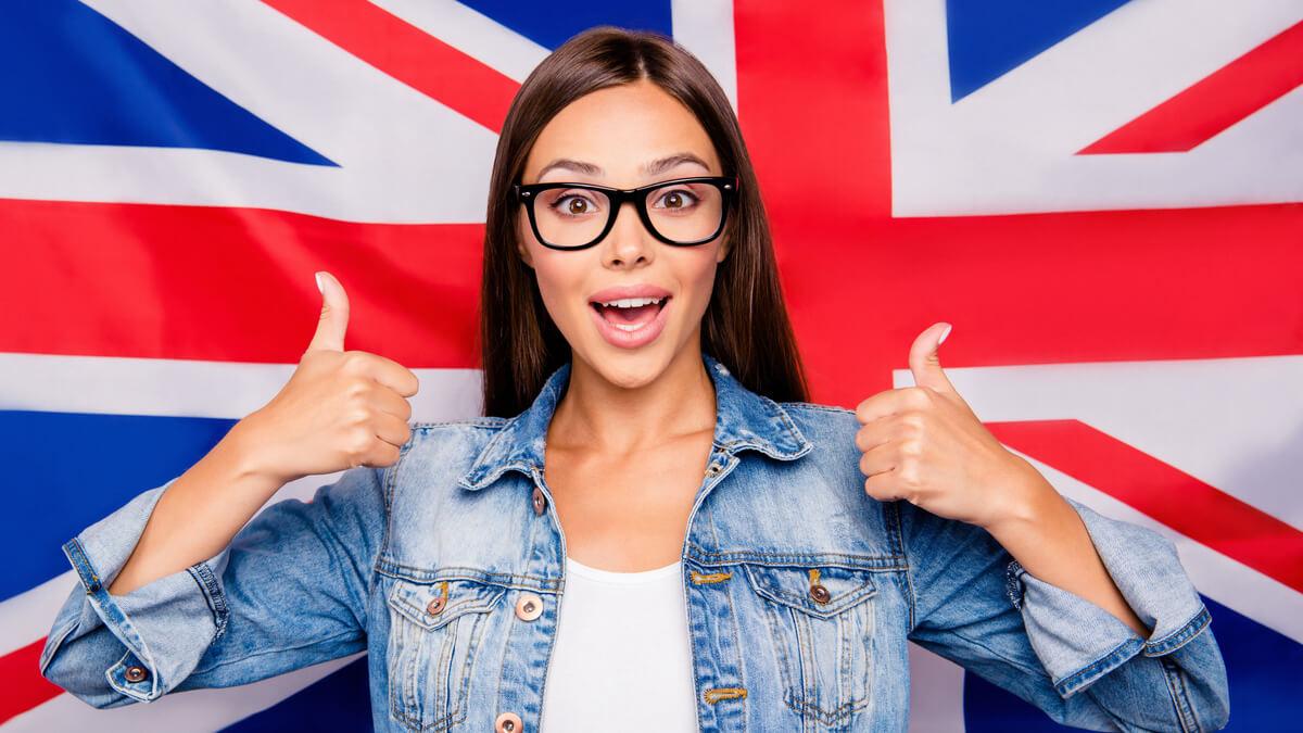 moça jovem de óculos com os dois polegares para cima na frente de uma bandeira do Reino Unido