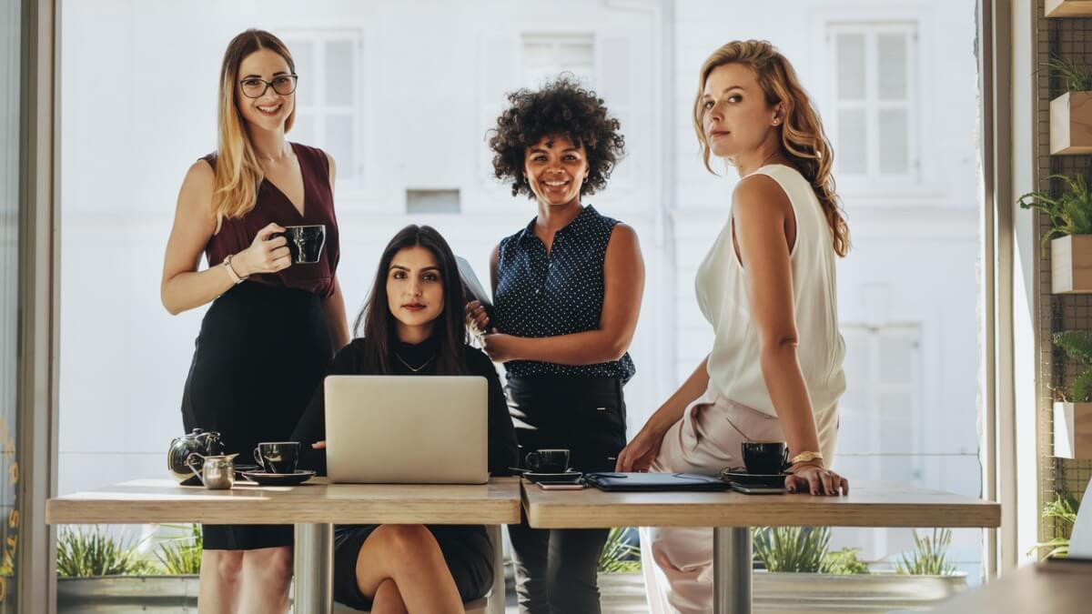 quatro mulheres de etnias diferentes olham para a frente, estando uma sentada em frente a um notebook e as outras três de pé.