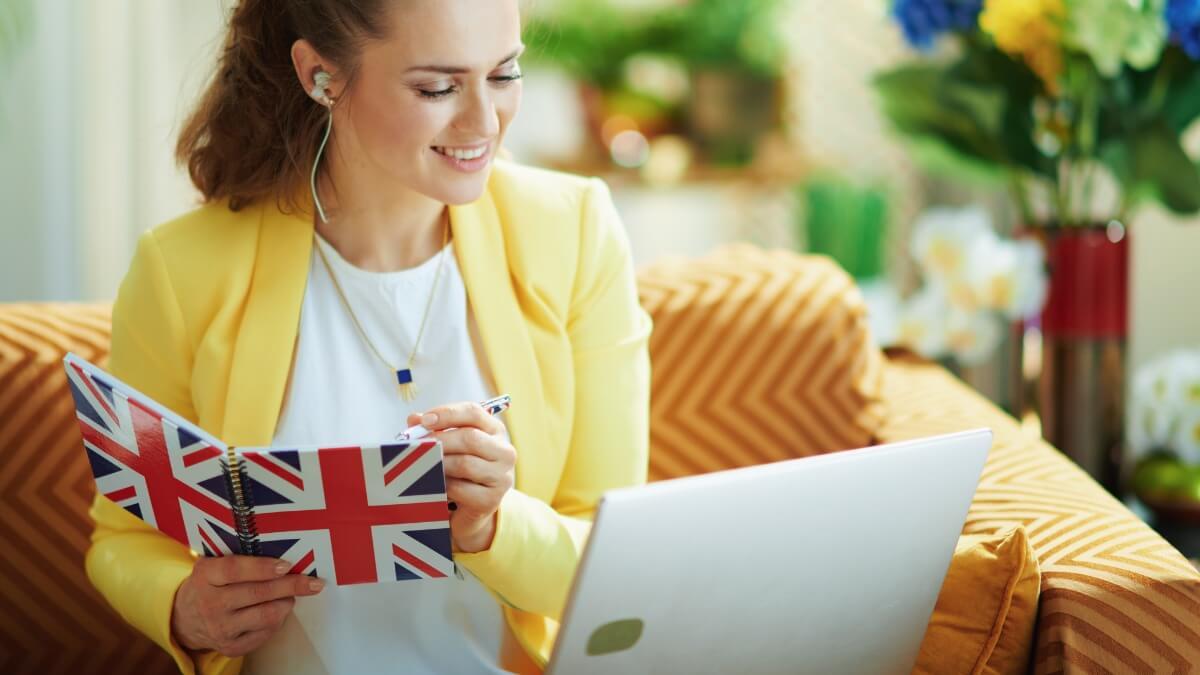 Mulher segurando um caderno com a bandeira do Grã Bretanha na capa, estuda usando um computador portátil à sua frente