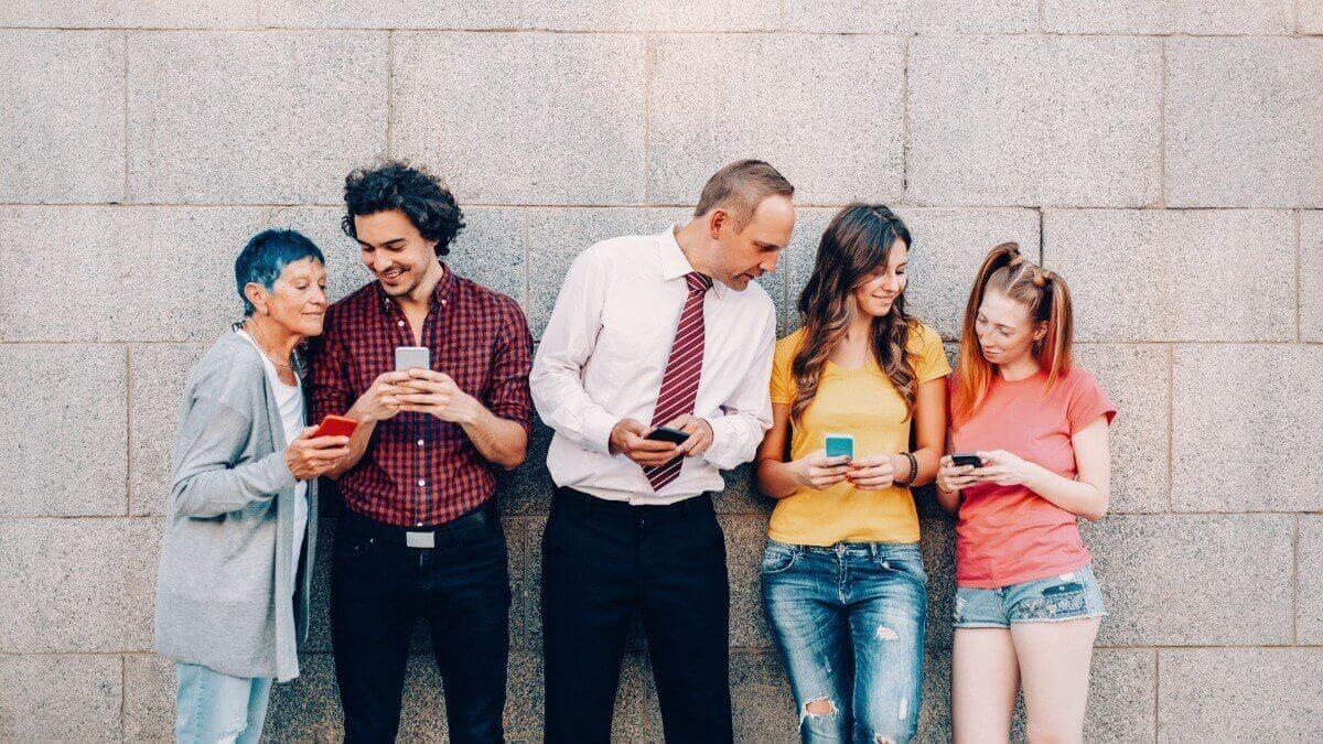 Cinco pessoas de diferentes gerações em frente a uma parede mexem em seus celulares