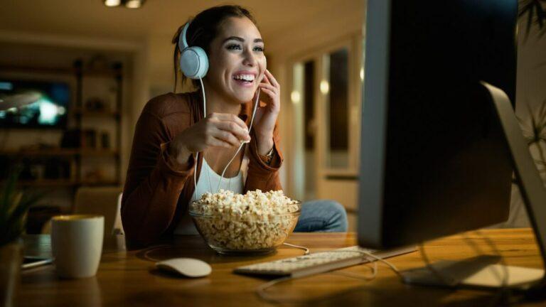 Mulher jovem comendo pipoca com fones de ouvido assistindo filme