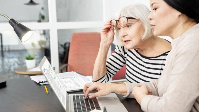 Senhora mais velha levanta o óculos ao olhar para o computador enquanto recebe uma aula de inglês de uma professora mais jovem que tenta lhe ensinar a pronunciar as palavras corretamente.