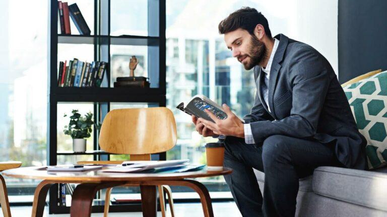 homem sentado ao sofá lê um livro à frente de uma mesa cheia de livros