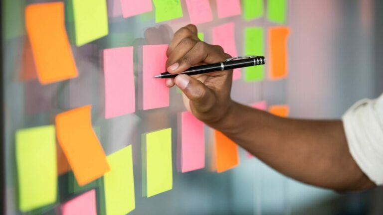Uma pessoa praticando o vocabulário de inglês enquanto escreve em um post it