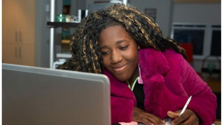 Adolescente com roupas de inverno estuda inglês em frente ao computador