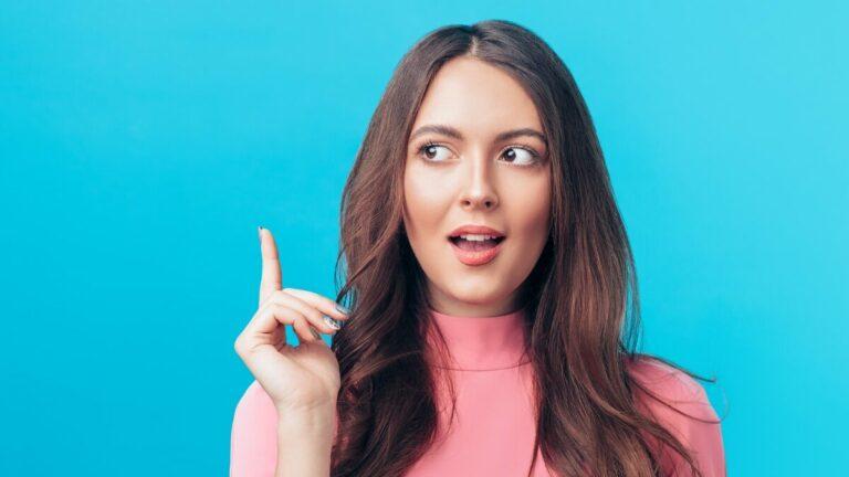 Fundo azul, à frente uma mulher com uma blusa rosa aponta o dedo para cima enquanto olha para o lado, tendo uma ideia