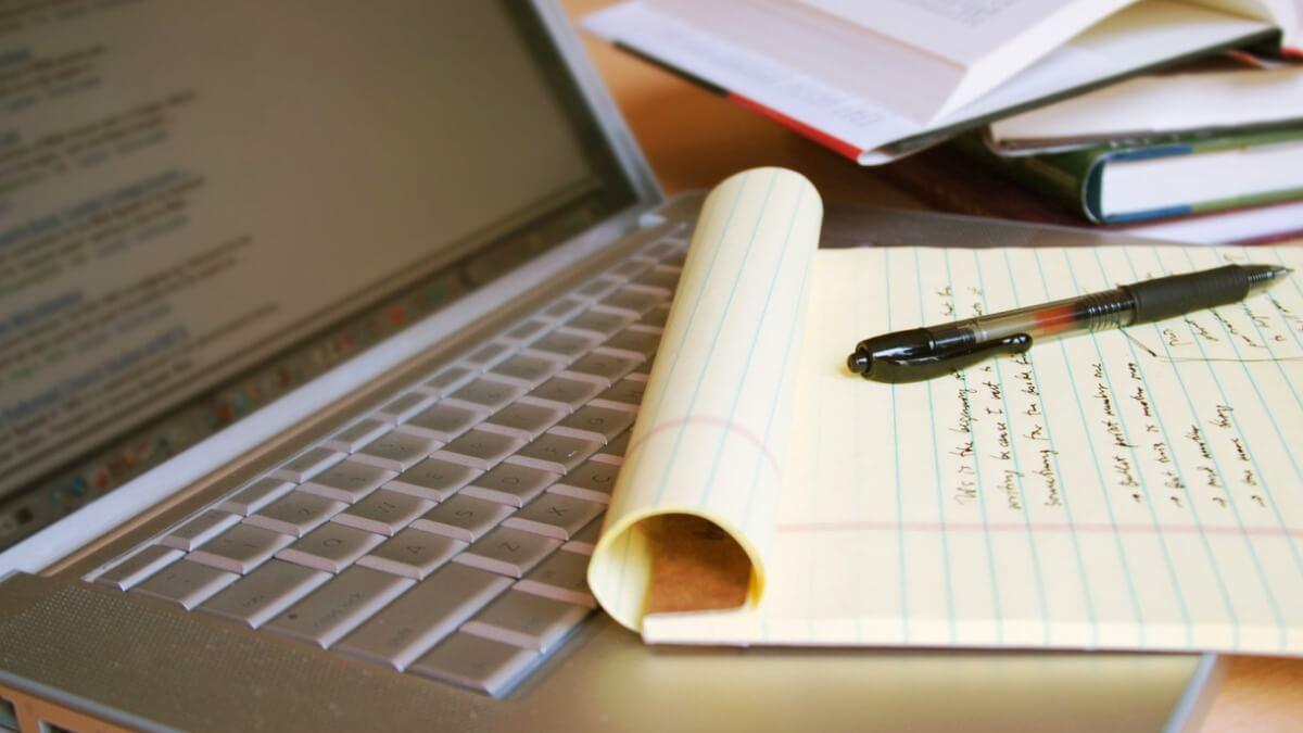 bloco de notas com anotações com uma caneta acima e um notebook aberto