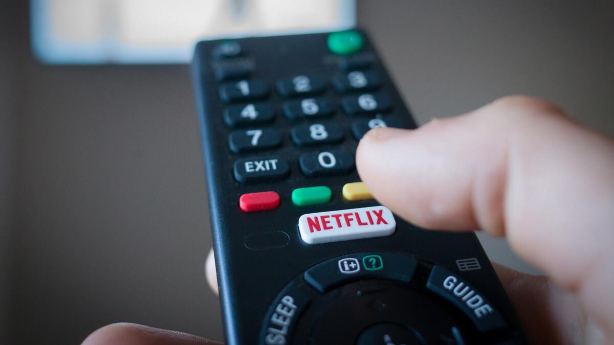 Mão segurando um controle remoto direcionado à Smart TV