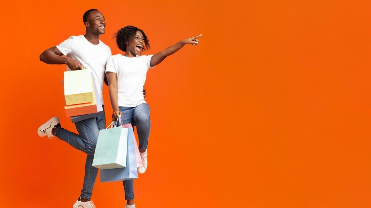 Homem e mulher vibram com sacolas de compras a frente de um fundo laranja