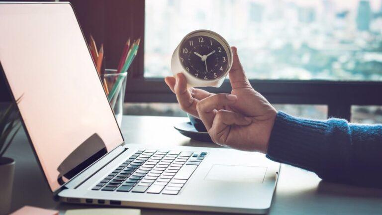 Mão segurando um relógio na frente de um notebook