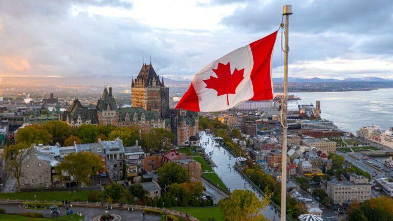 Uma bandeira do Canadá tremulando com a cidade de Quebec e o rio Saint Lawrence ao fundo
