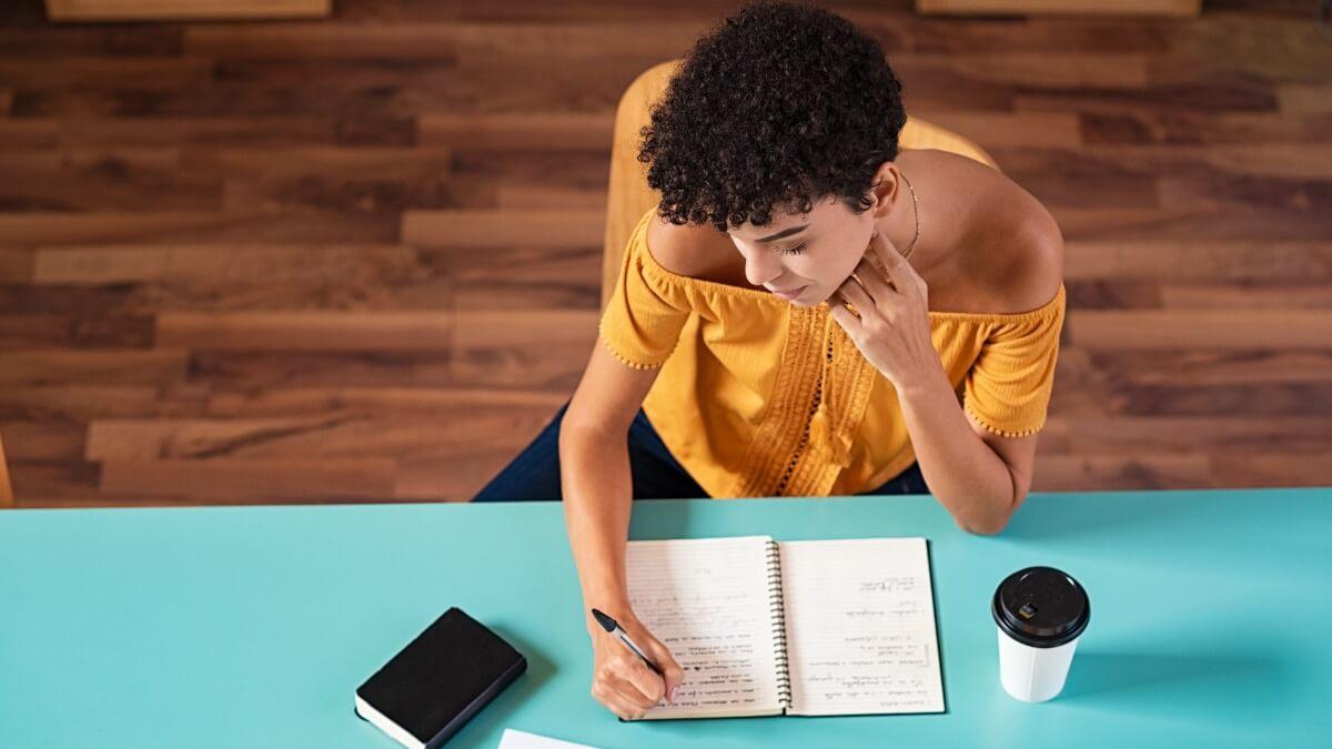 mulher vista de cima pratica escrita em inglês em um caderno