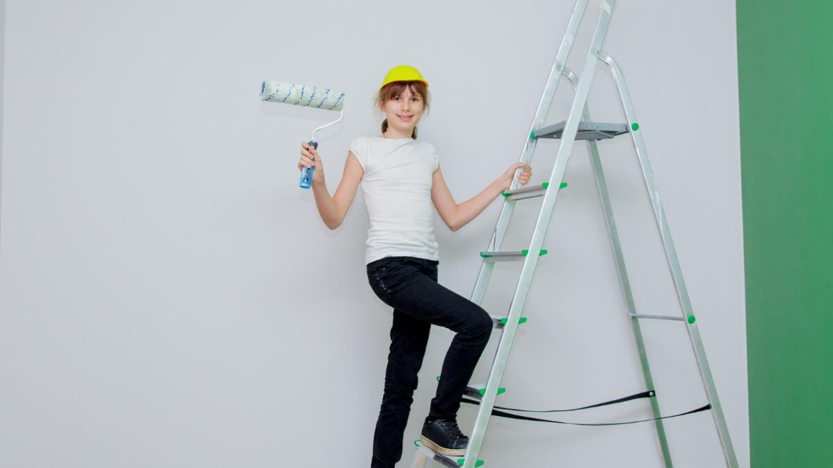 menina subindo em uma escada móvel segura em sua mão direita um rolo de pintar.
