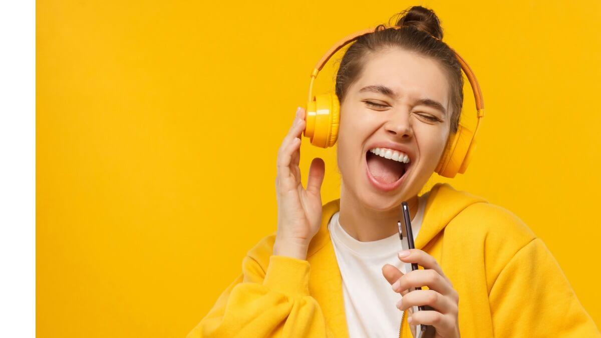 Garota jovem com fone de ouvindo cantando com um celular na mão à frente de um fundo amarelo
