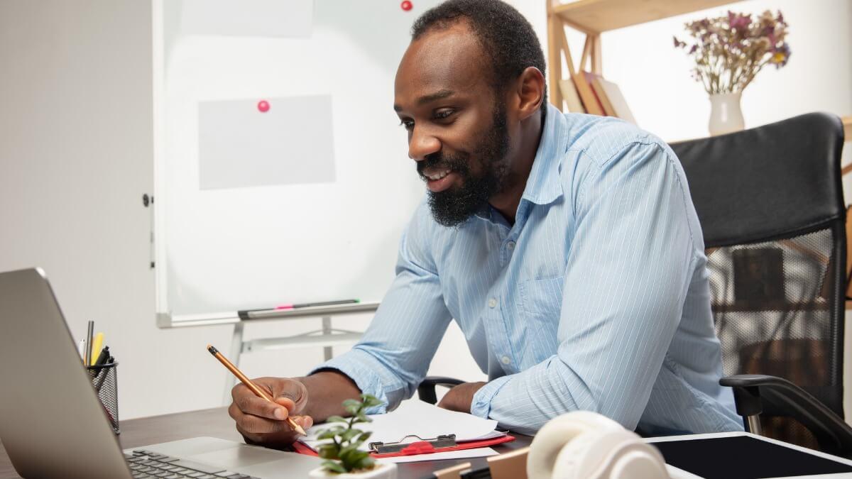 homem negro com barba estuda inglês de forma online em frente a um laptop