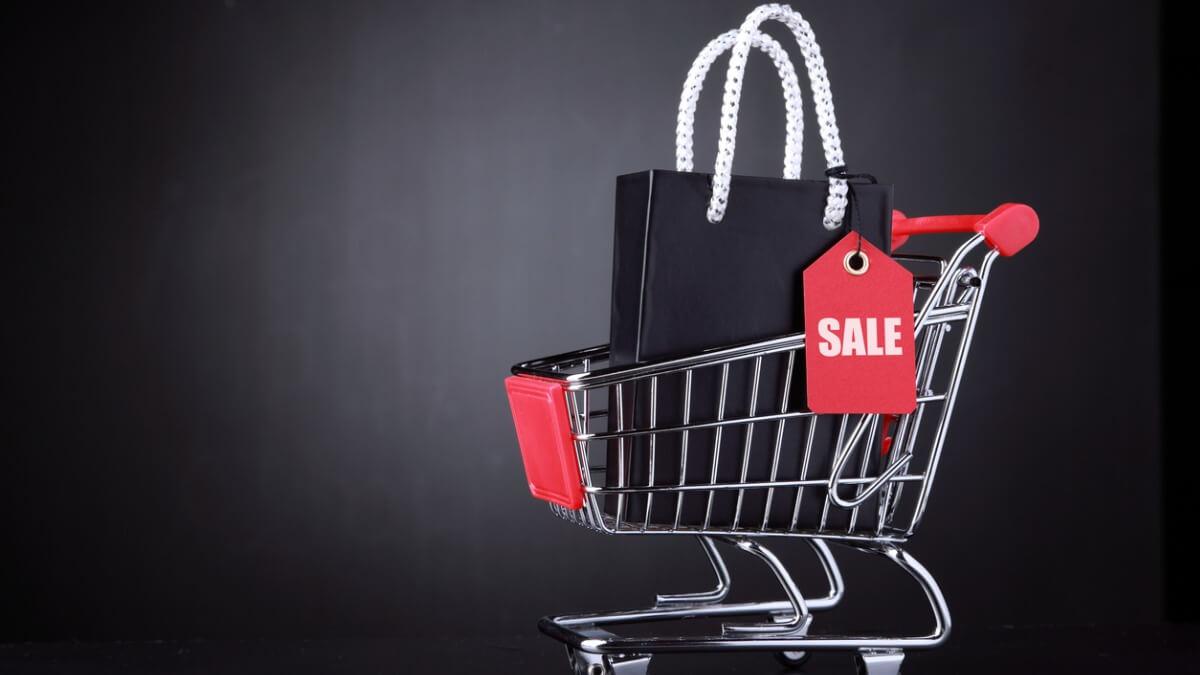 um carrinho de compras com apenas uma sacola grande dentro dele, preta, com uma etqiueta vermelha escrito sale.