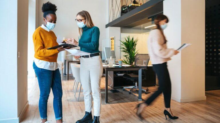 Uma mulher negra conversa com uma mulher branca, no meio de um escritório, usando máscaras de proteção facial