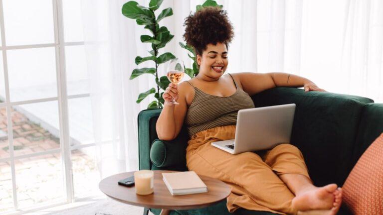 Mulher deitada no sofá bebe vinho enquanto assiste um série no notebook, que está no seu colo.