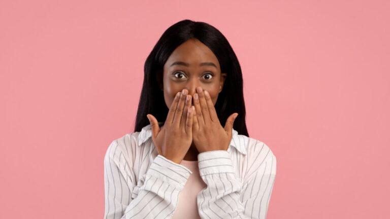 Moça negra à frente de um fundo cor de rosa coloca as duas mãos em frente da boca com expressão de surpresa e choque