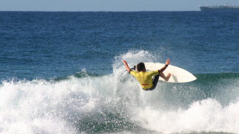 Atleta de surfe fazendo uma manobra radical em uma onda