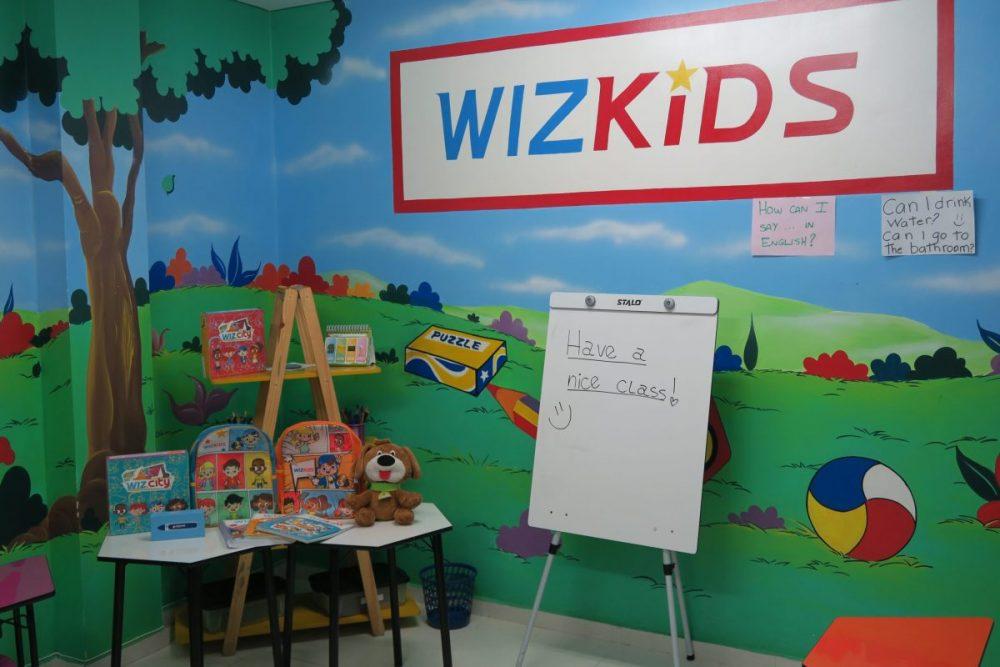 Recepção com sofás, computadores e escada na escola de idiomas Wizard by Pearson