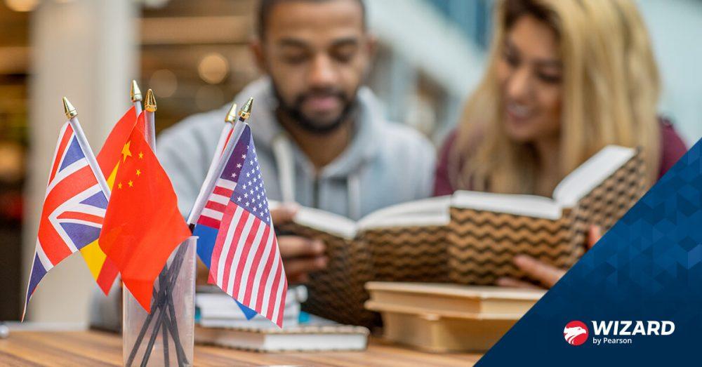 Homem e mulher lendo livro e bandeiras de vários países sobre a mesa
