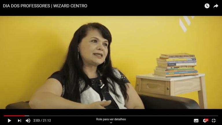 Professora de inglês Wizard Guarulhos sentada à esquerda com cabelos pretos soltos e livros à direita